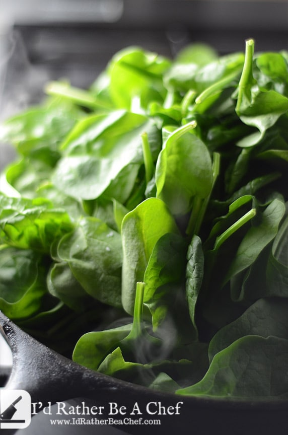 raw spinach added to the shallots and bacon fat for this sauteed spinach recipe