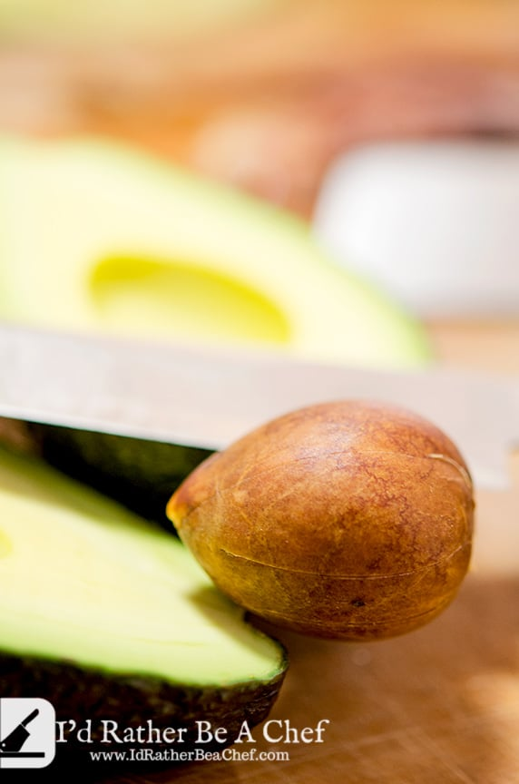 The third step in how to peel avocado is to remove the pit with the blade of your knife.