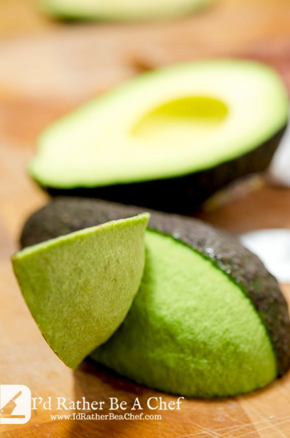 The fourth step in how to peel avocado is to slice the skin with a shallow cut and peel back the sections.