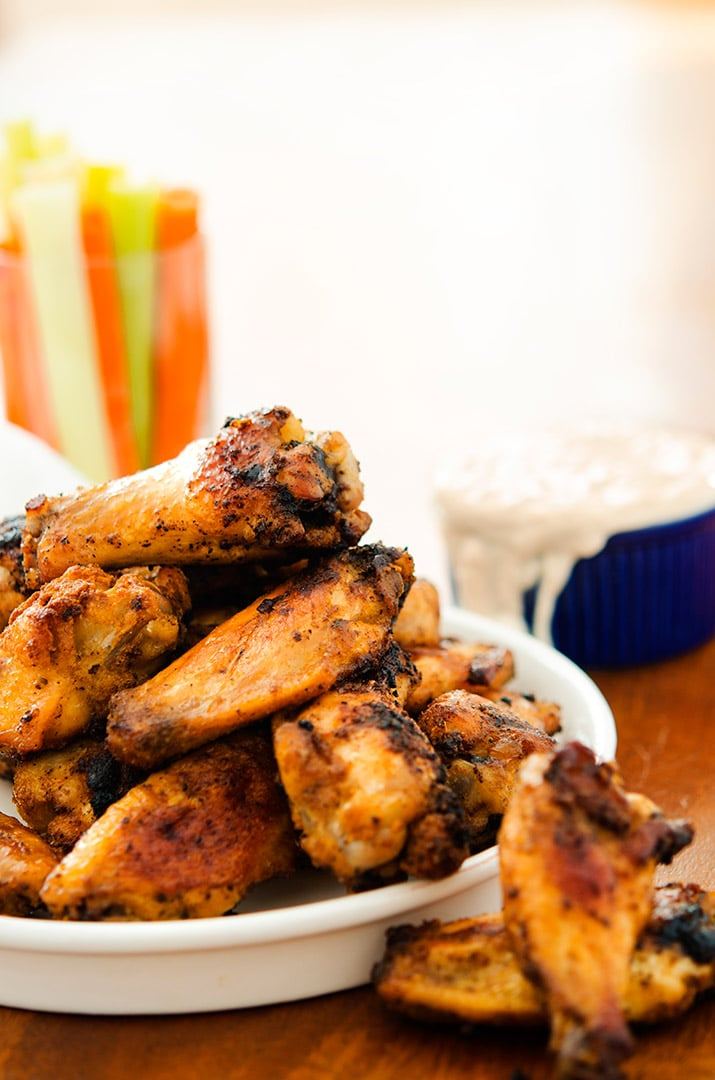 This crispy baked chicken wings recipe uses a dry rub for flavor and blue cheese sauce to kick it up!