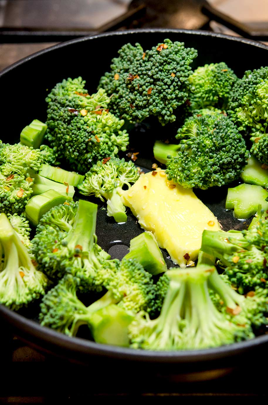 To prepare this Italian Broccoli Recipe, first add all the ingredients into the pan, including the red pepper flakes, garlic, butter and water.