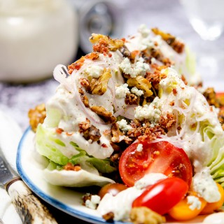 This is the ultimate iceberg wedge salad with homemade blue cheese dressing, crumbly bacon bits, brown butter walnuts, shallots and more...