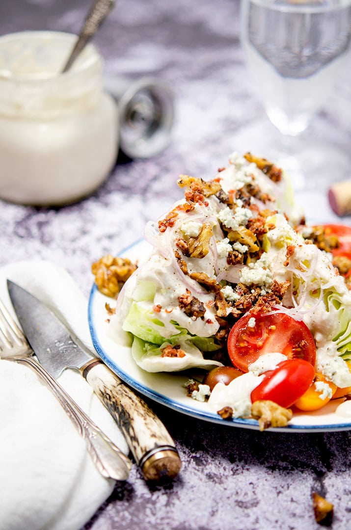 The perfect iceberg wedge salad has blue cheese dressing, bacon bits, shallots, butter drunk walnuts and fresh tomatoes. Don't forget the blue cheese crumbles too!