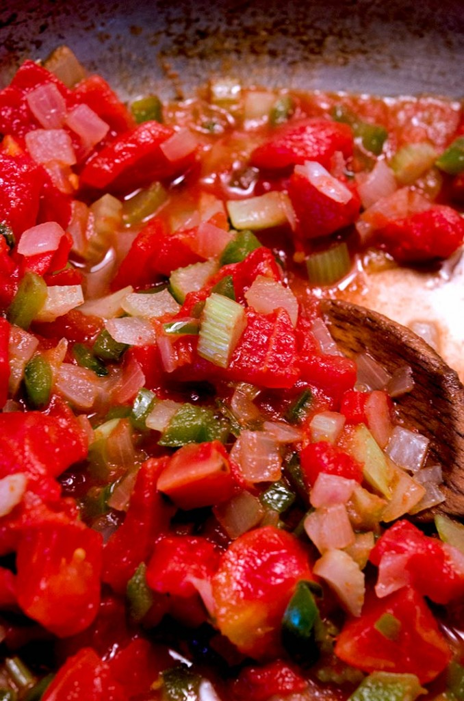 Add in the canned tomatoes and dried spices. Let the tomato juice soak up the spice to start the shrimp creole sauce.