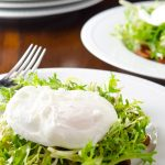Frisee salad with a poached egg and bacon lardons, ready to eat.