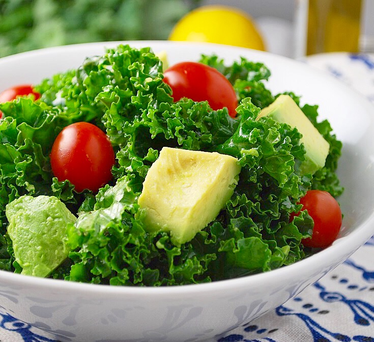 Marinated kale with avocado and tomatoes is the perfect salad to go with your low carb dinner recipes. Yum.