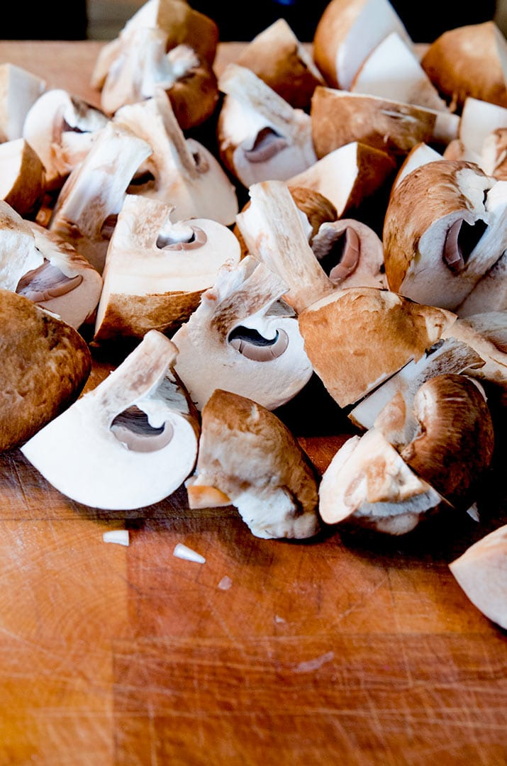 To make sauteed mushrooms first the need to be cleaned and quartered.