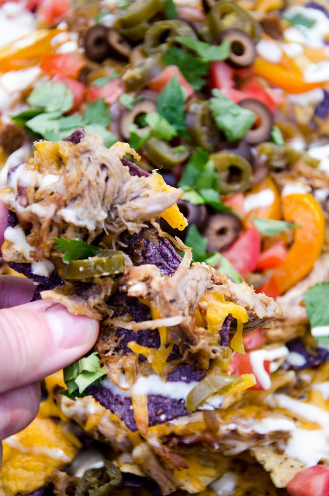 Fajita nachos are piled high with delicious ingredients like cilantro, tomato, cheese, olives, sauteed onions and peppers and more!