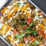 Fajita nachos are delicious when layered with cheese, pulled pork, onions, peppers and creme fraiche. Awesome.
