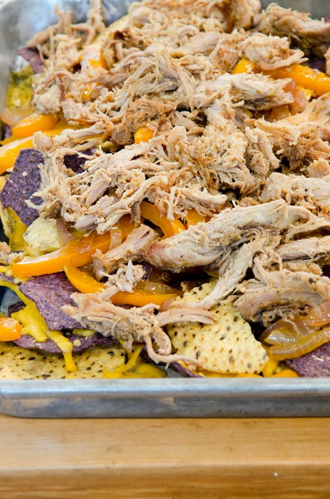 Fajita Nachos Step 2: Add another layer of chips, more cheese, the pork and some peppers and onions. Back into the oven then!