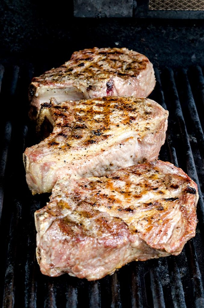 Grilling pork chops to perfection requires flipping and rotating the meat to get perfect sear marks.