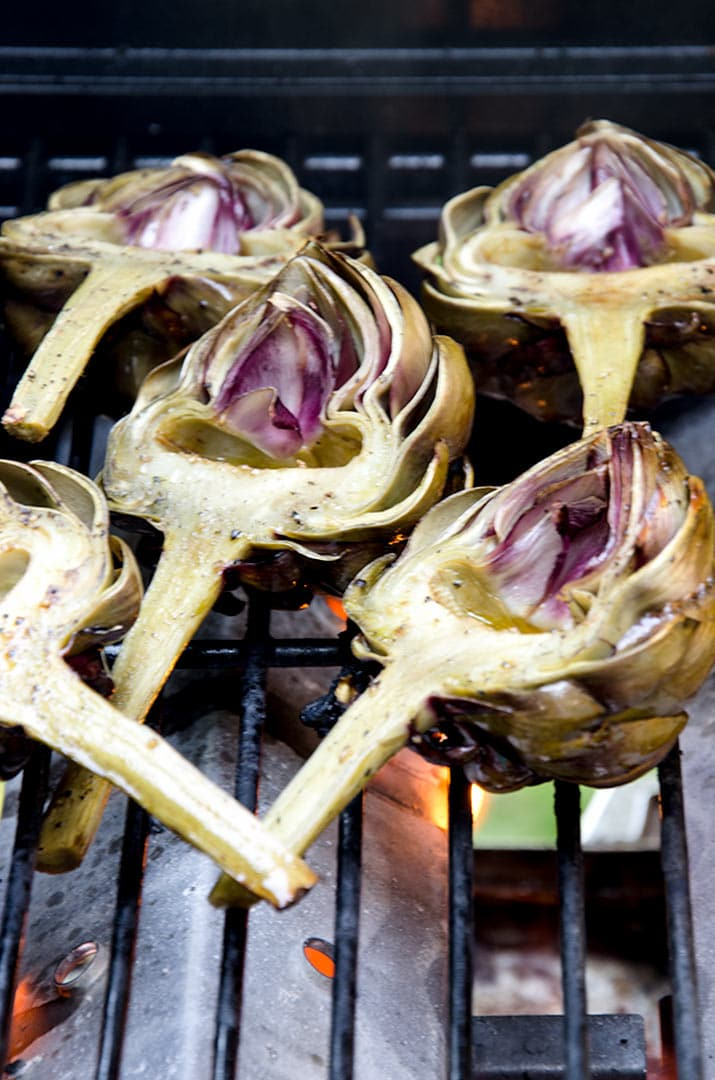 Making grilled artichokes takes a bit of time to steam them in foil first and then grill them to enhance the flavors. Sweet, tender and delicious is the outcome.