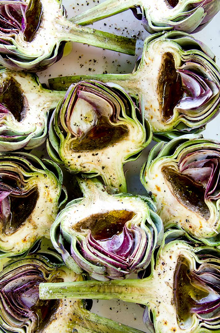 Grilled artichokes are best when they are seasoned simply. These have olive oil, red wine vinegar, salt and pepper. Delicious and simple.