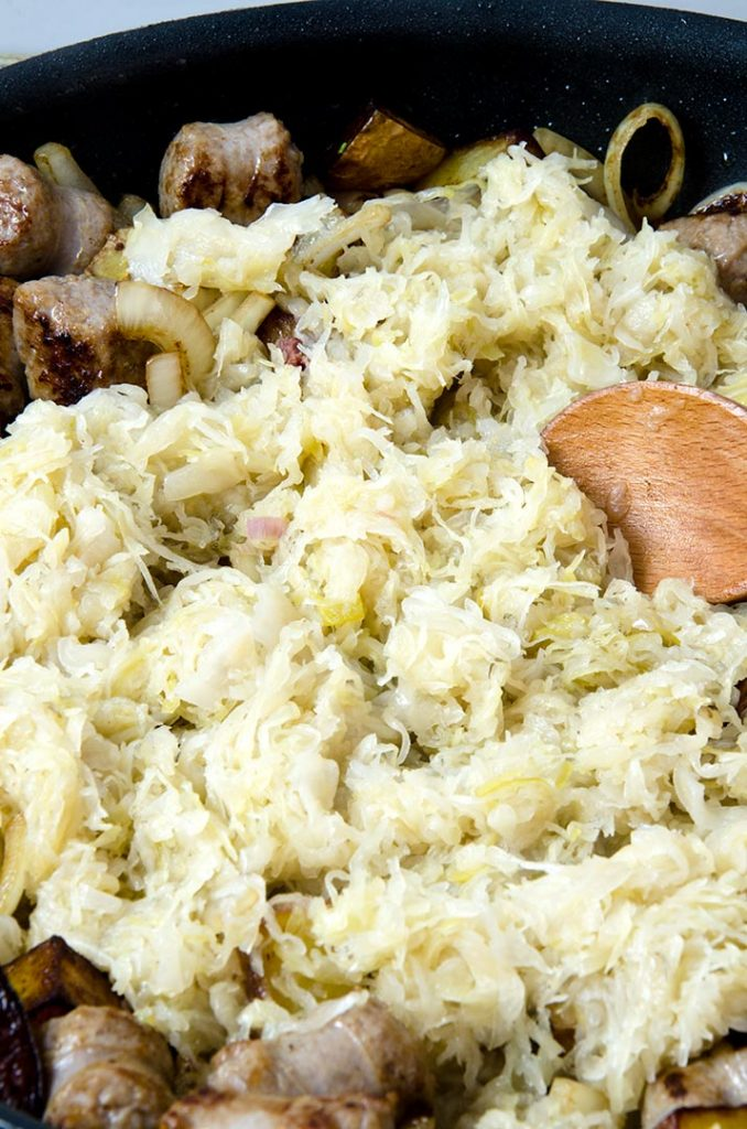 The key to good sausage and sauerkraut is to add the sauerkraut to a hot pan, then reduce the heat. It will brown nicely without burning.