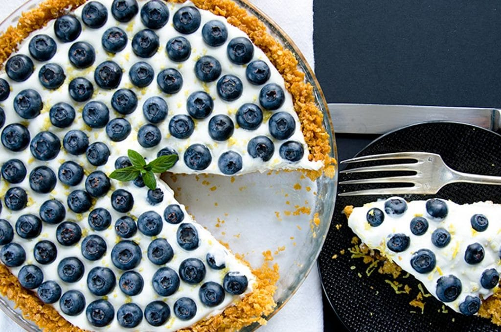 No bake cheesecake with a thin layer of vanilla whipped cream, lemon zest and fresh blueberries.