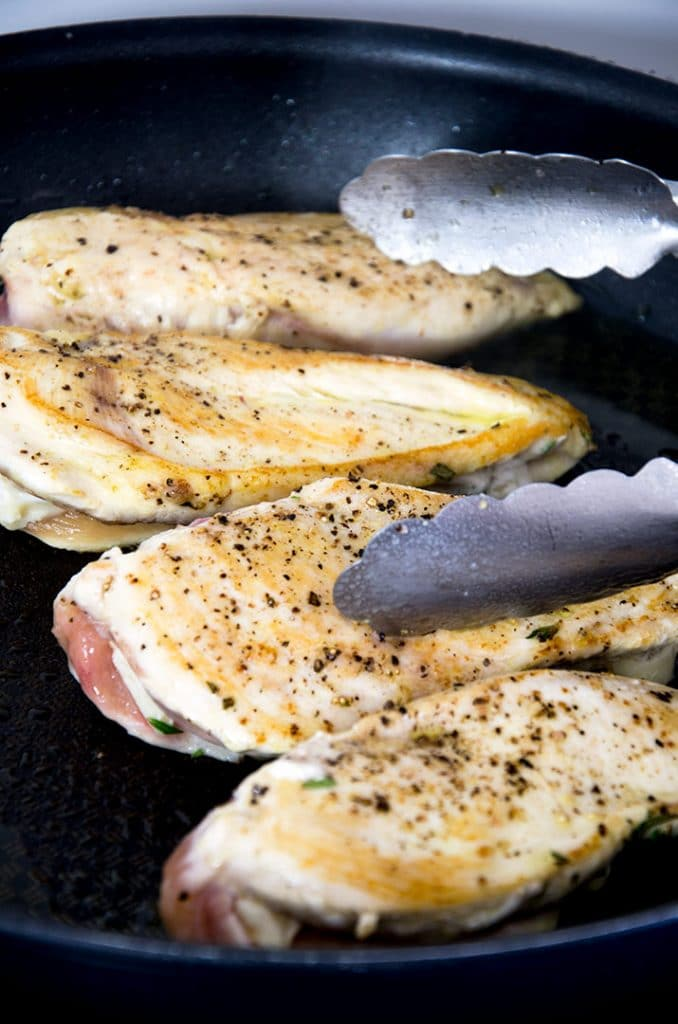 A stuffed chicken breast recipe that starts by sauteeing the chicken until it is golden brown.