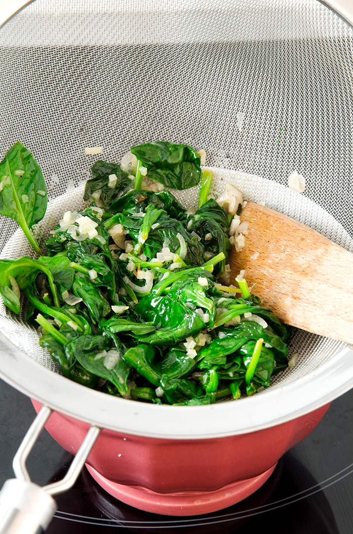 The perfect chicken saltimbocca stuffing starts with drained sauteed spinach.