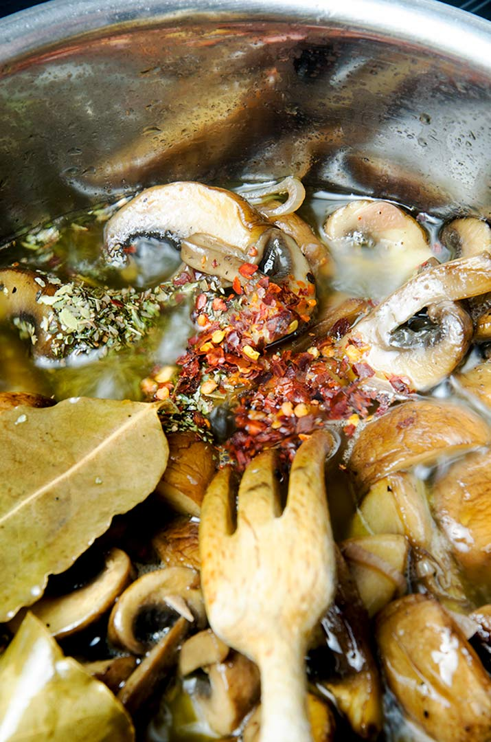 Adding red pepper flakes and dried oregano to marinated mushrooms really brings out the flavor.