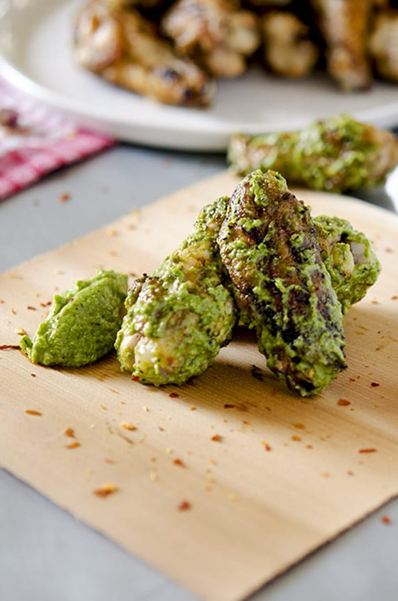 Pesto chicken wings are delicious with red pepper flakes.